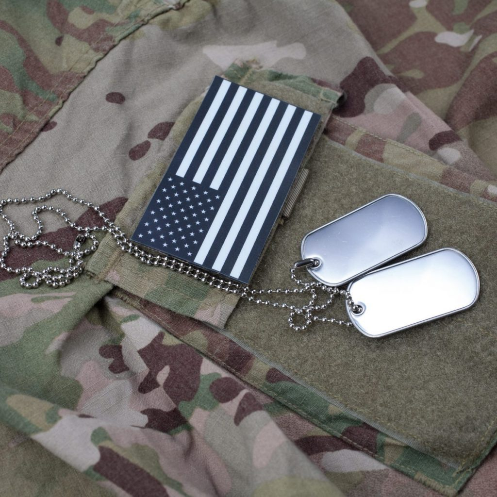 Operational Camouflage Pattern US service uniform overlaid with subdued American Flag patch and dog tags. Service members like these deserve expert representation by an experienced military lawyer