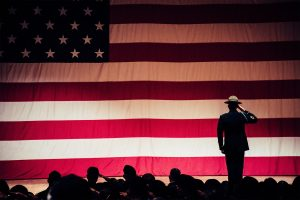 Drill Sergeant salutes in front of US flag