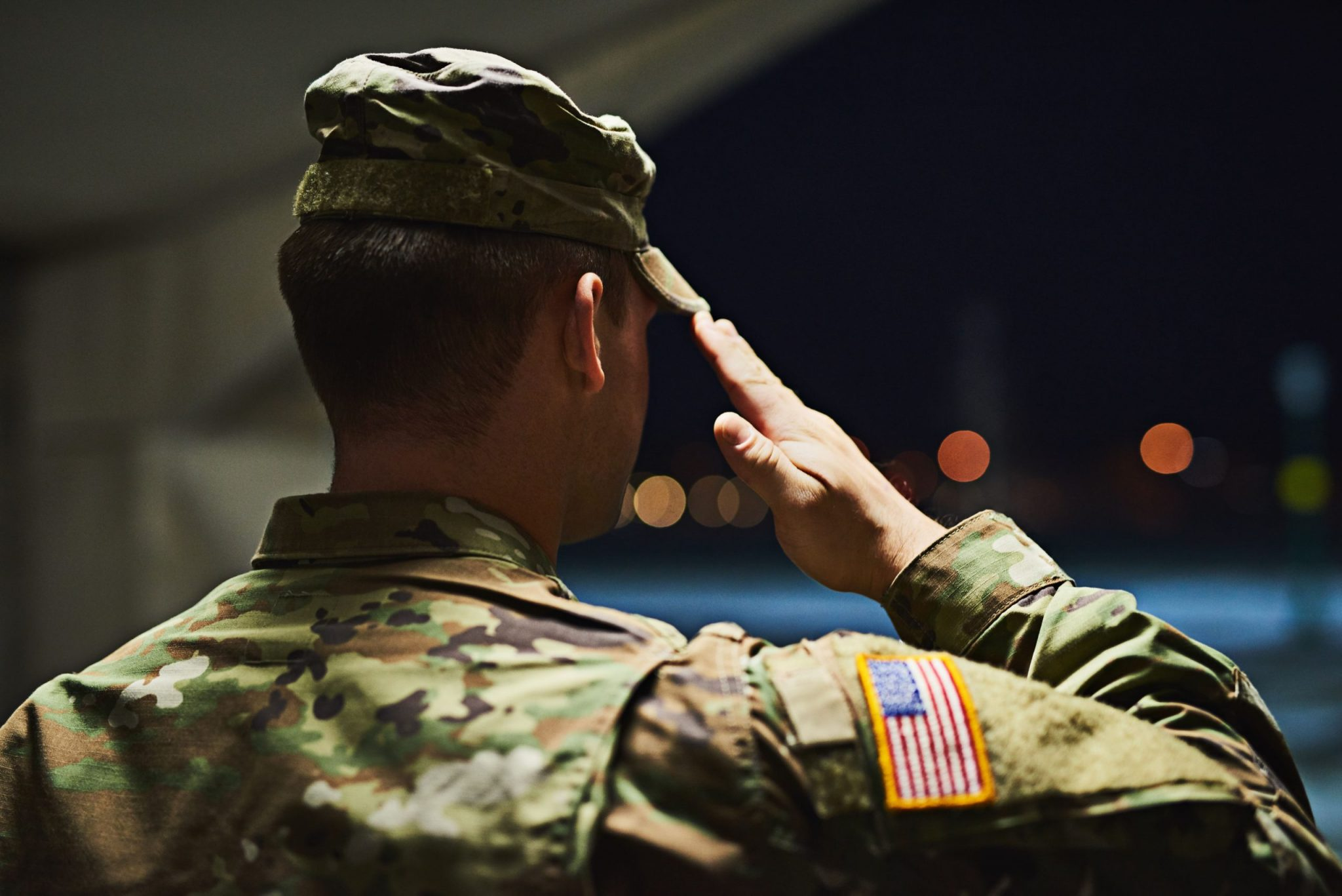 Officer saluting inside a hanger facing the outdoors at night; lawyers specializing in military law near me
